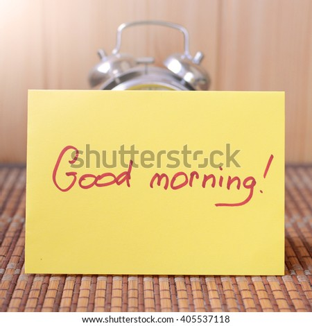 Alarm clock and a piece of paper that says good morning. - stock photo
