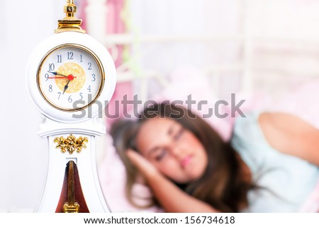Alarm clock and a student sleeping in the background