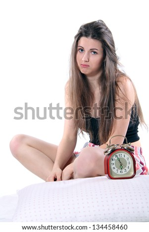Alarm clock and beautiful girl with sad expression . Unhappy wake up concept