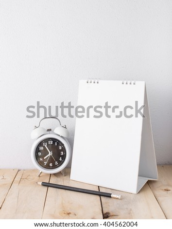 alarm clock and desktop calendar with wooden floor on white background - stock photo