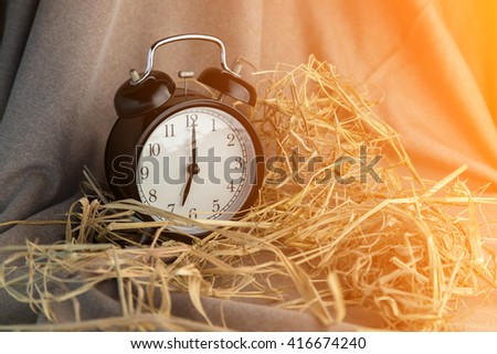 Alarm clock and dry hay. Photo in retro color style. - stock photo