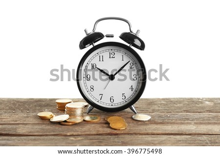 Alarm clock and money coins on wooden table. - stock photo
