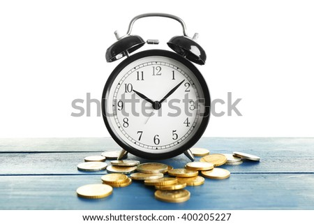Alarm clock and money coins on wooden table.