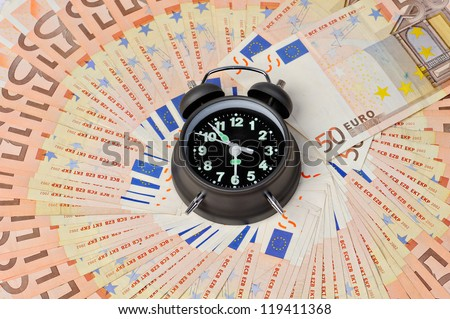 alarm clock and on euro background - stock photo