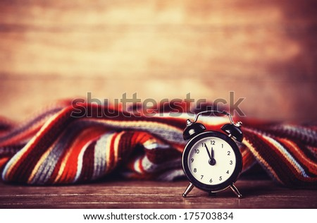 Alarm clock and scarf. Photo in retro color style. - stock photo