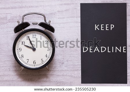 Alarm clock and sing indicating to keep deadline  - stock photo