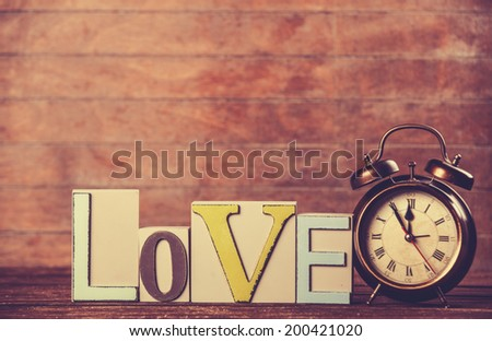Alarm clock and word Love on wooden table. - stock photo