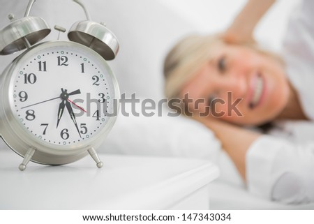 Alarm clock annoying blonde woman in bed blocking her ears