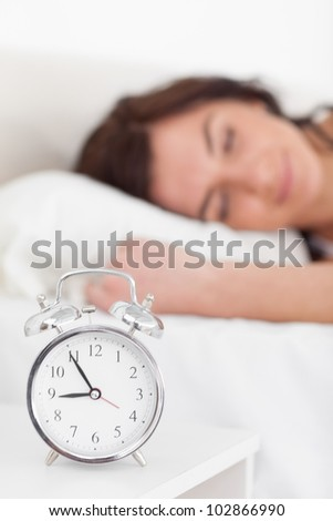Alarm clock being placed on a nightstand in a bedroom