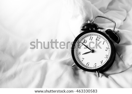 Alarm clock black style vintage place on a bed of soft white.