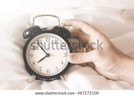 Alarm clock black style vintage place on a bed with hands of a man holding a clock.Vintage tone