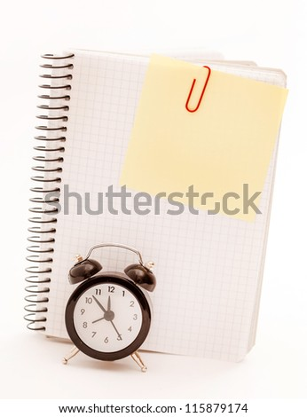Alarm clock, blank notebook sheet on the white