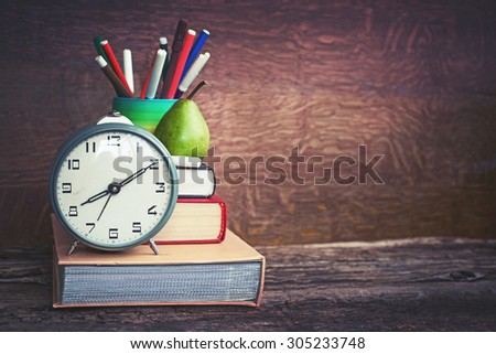 Alarm clock, book stack and felt pens. Schoolchild and student studies accessories. Back to school concept. - stock photo
