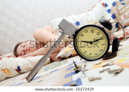 Alarm clock broken by a hammer against the sleeping girl