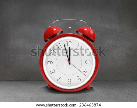 Alarm clock counting down to twelve against grey room - stock photo
