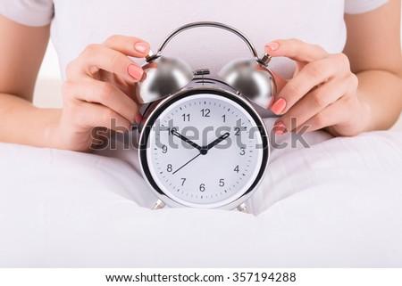 Alarm clock. Female hands touching the alarm clock - stock photo