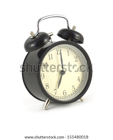 Alarm clock in black case shows 7 o'clock. Side view isolated on white close up
