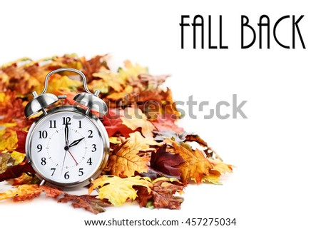 Alarm clock in colorful autumn leaves isolated against a white background with light shadow and shallow depth of field. Daylight savings time concept. - stock photo