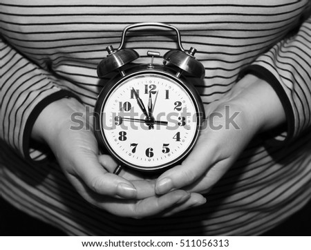 alarm clock in female hands