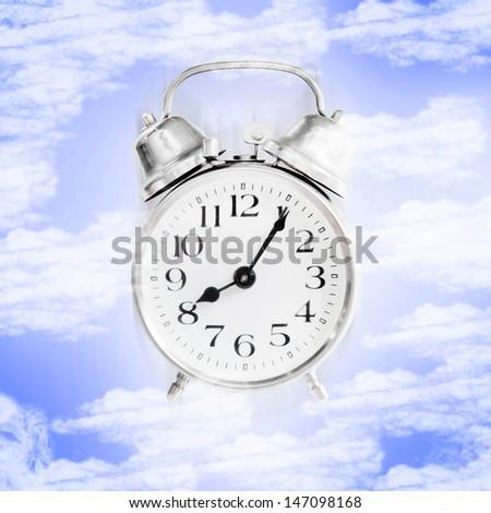 Alarm clock in the blue sky. - stock photo