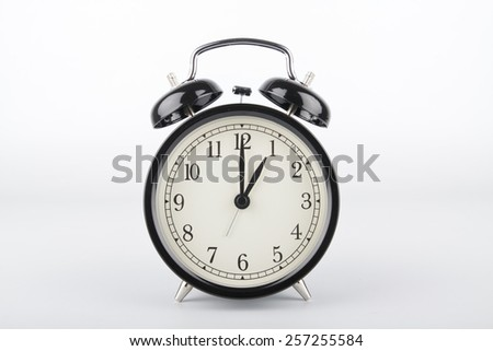Alarm clock is showing the right time. One o'clock. - stock photo