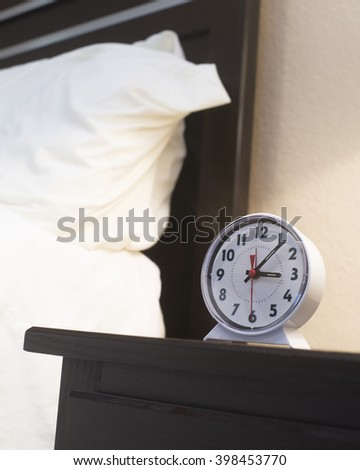 Alarm clock next to bed/Alarm Clock/Early morning set on an alarm clock which is next to a bed - stock photo