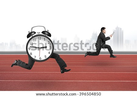 Alarm clock of running legs running after man holding tablet, on red running track with city skyline background.