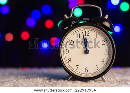 Alarm clock on a background of holiday lights. Christmas concept. - stock photo