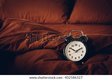 Alarm clock on a bed.Vintage retouching.