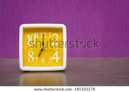alarm clock on a wooden table in front of purple wall - stock photo