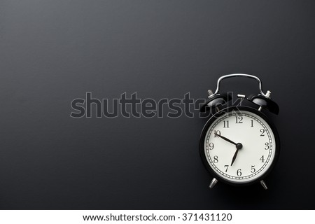 alarm clock on black background - stock photo