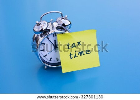 alarm clock on blue table with sticky note 'tax time' - stock photo