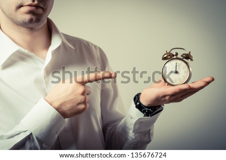 Alarm clock on businessman's hand, Time over concept