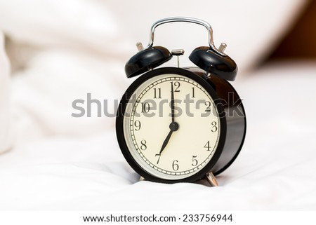Alarm clock on messed bed.