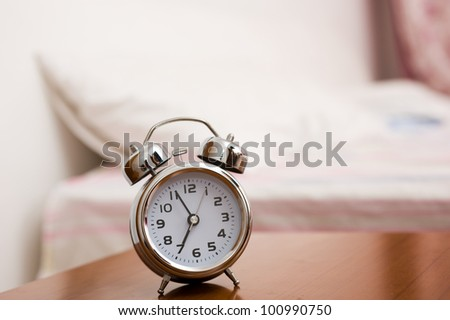 Alarm clock on night table at bed - stock photo