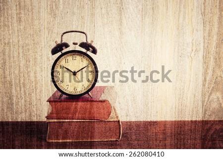 Alarm clock on old book on table. Grunge wood Vintage filter. - stock photo