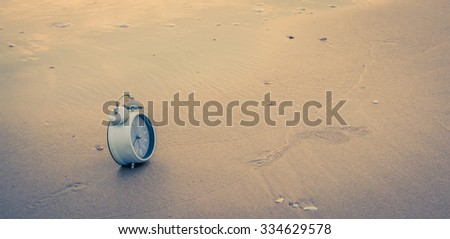 alarm clock on sand with wave and sea in soft focus in background. Macro with extremely shallow dof. Selective focus limited to edges of clock. - stock photo