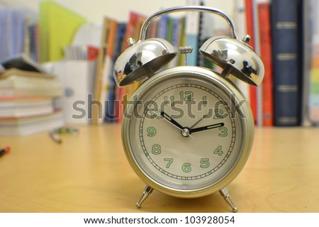 alarm clock on study desk - stock photo