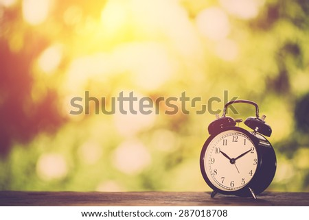 Alarm clock on table with booked green leaf background. Vintage filter. - stock photo