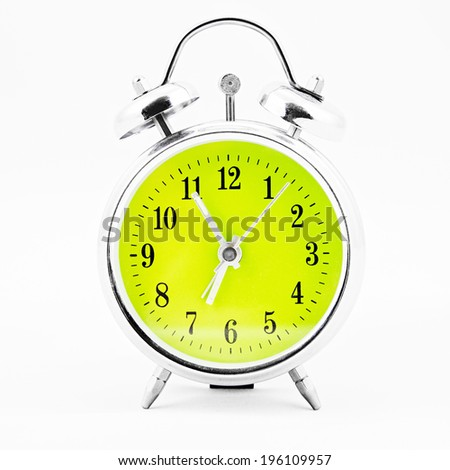 Alarm clock on white background. Showing time five minutes before seven