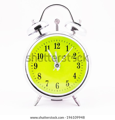 Alarm clock on white background. Showing time five minutes before twelve
