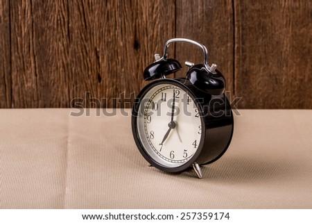 Alarm clock on wood background. - stock photo