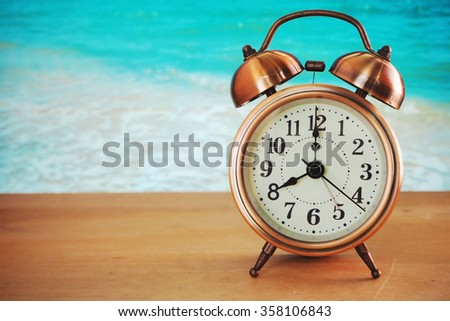 Alarm Clock on Wood Floor and Ocean Background.