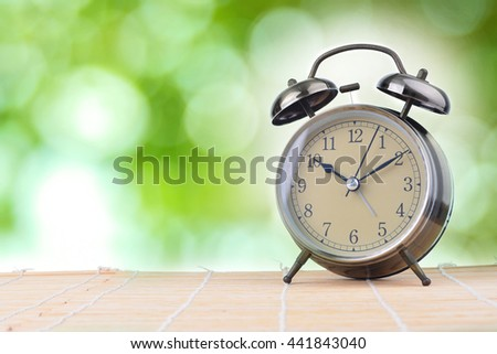 Alarm clock on wood with blurry green bokeh in background. Concept of time