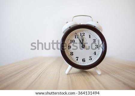 Alarm clock on wooden table - stock photo