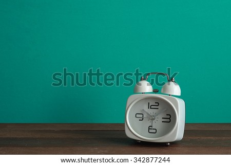 Alarm clock on wooden table front mint green background. Vintage effect. - stock photo