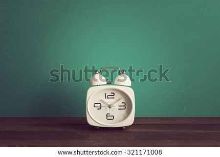 Alarm clock on wooden table front mint green background with copyspace. Vintage effect. - stock photo
