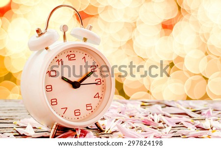 Alarm clock on wooden table with bokeh background soft focus.