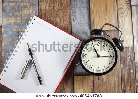alarm clock on wooden table with book and pen - stock photo