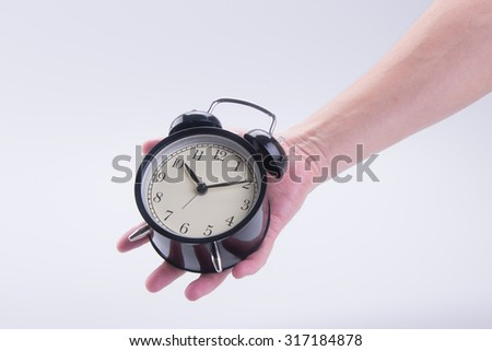 alarm clock or alarm clock with hand on the background